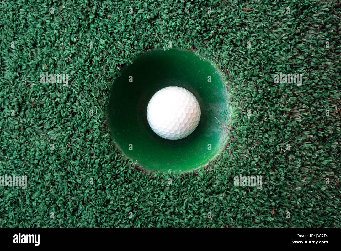 Mini golf scene with ball and hole. Can be used like background. Sunny day at resort park Stock Photo