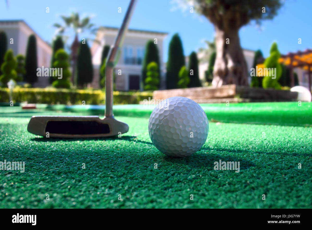 Mini golf scene with ball and club. Sunny day at resort park Stock Photo