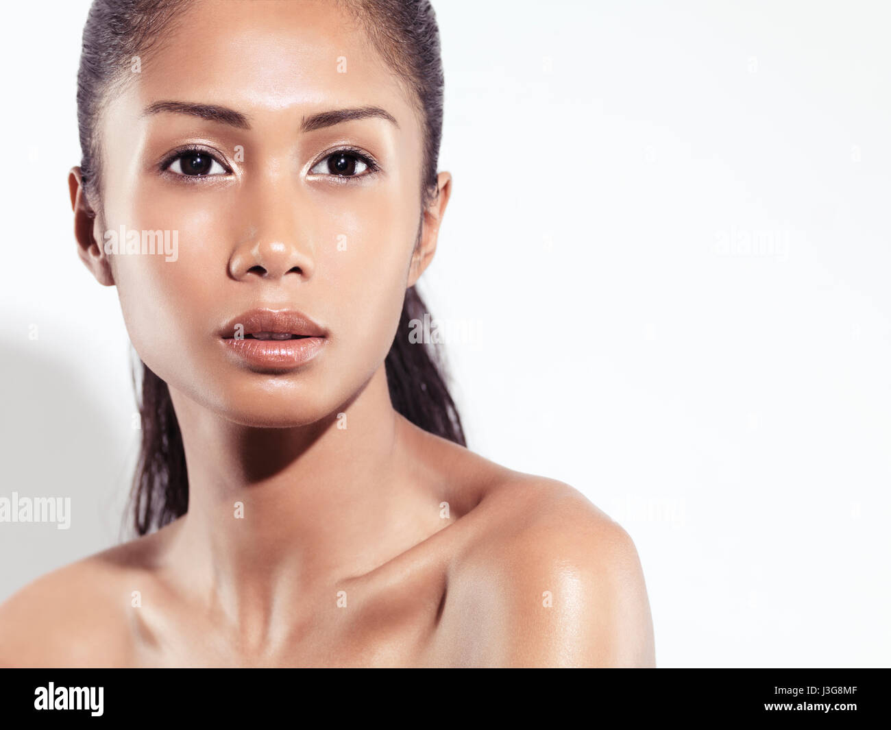 Closeup beauty portrait of an attractive young woman beautiful exotic asian face with healthy natural look isolated on white background Stock Photo