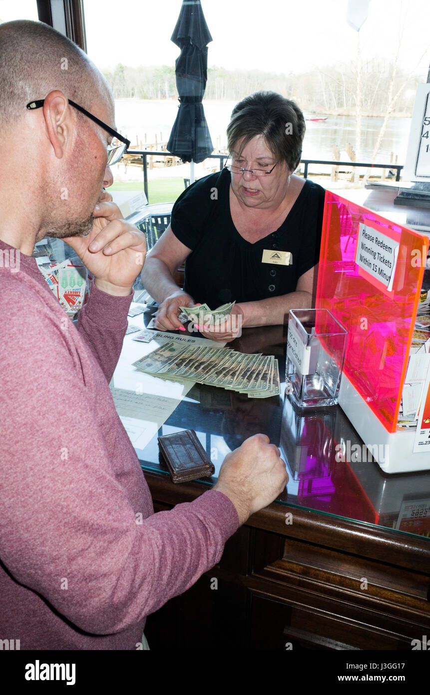 Man being paid by woman attendant for having a winning pull tab. Brainerd Minnesota MN USA - Stock Image
