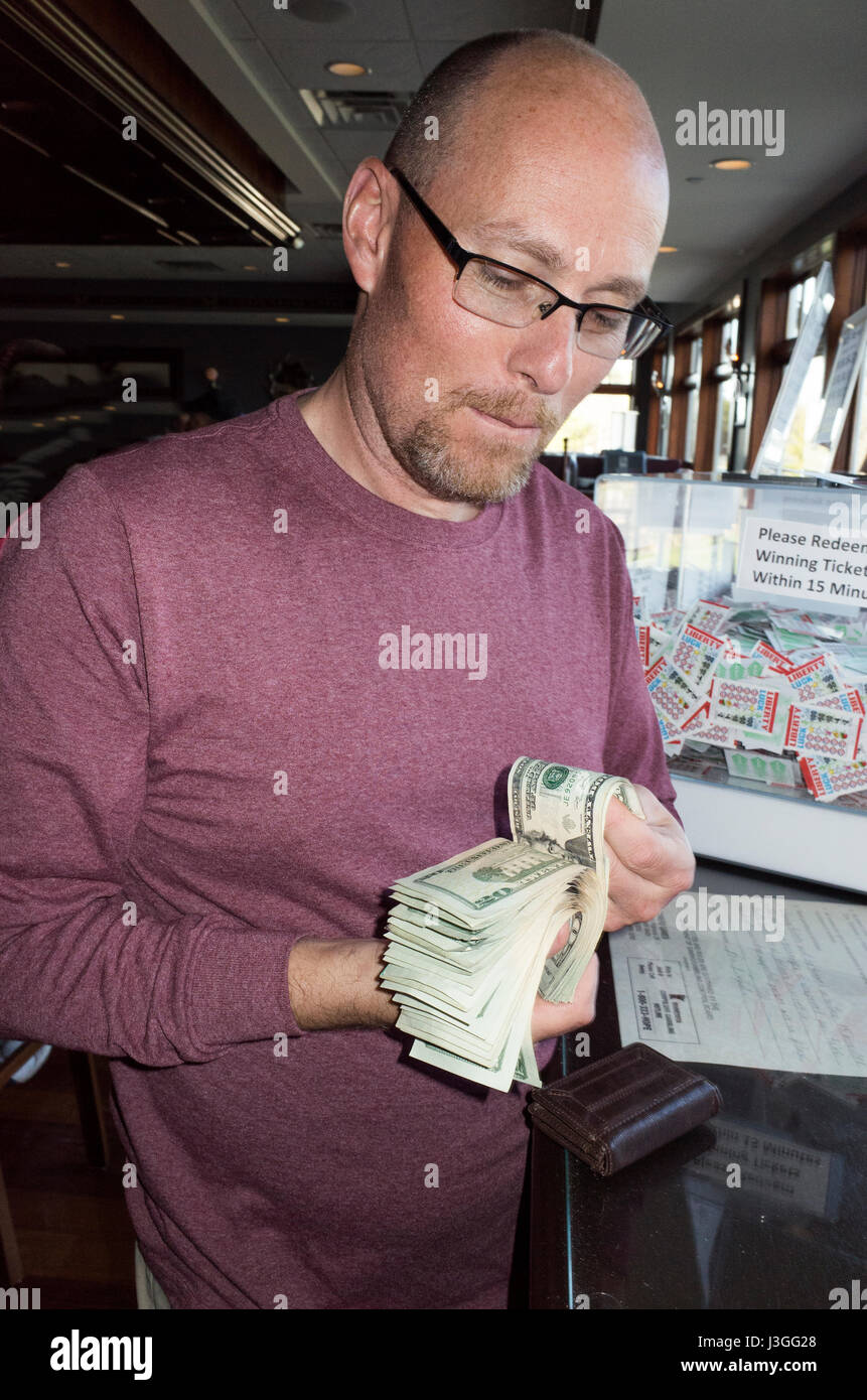 Man counting his money after coming up with the winning pull tab. Brainerd Minnesota MN USA - Stock Image
