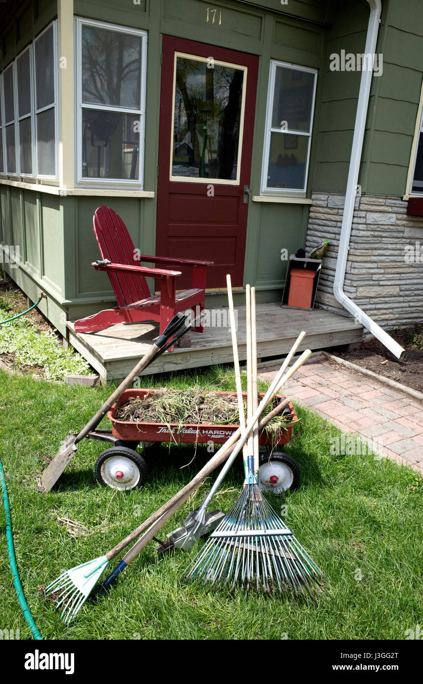 Front yard spring clean up with rakes, shovel, and wagon on hand. St Paul Minnesota MN USA - Stock Image