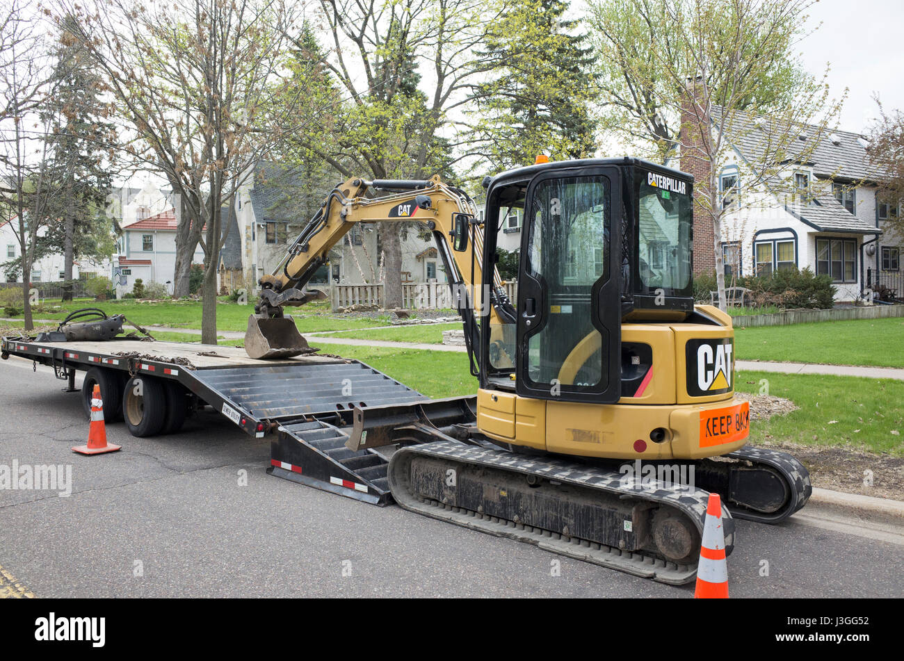 Front end loader driven by tank treads or continuous tracks ready to work on a residential neighborhood project. - Stock Image