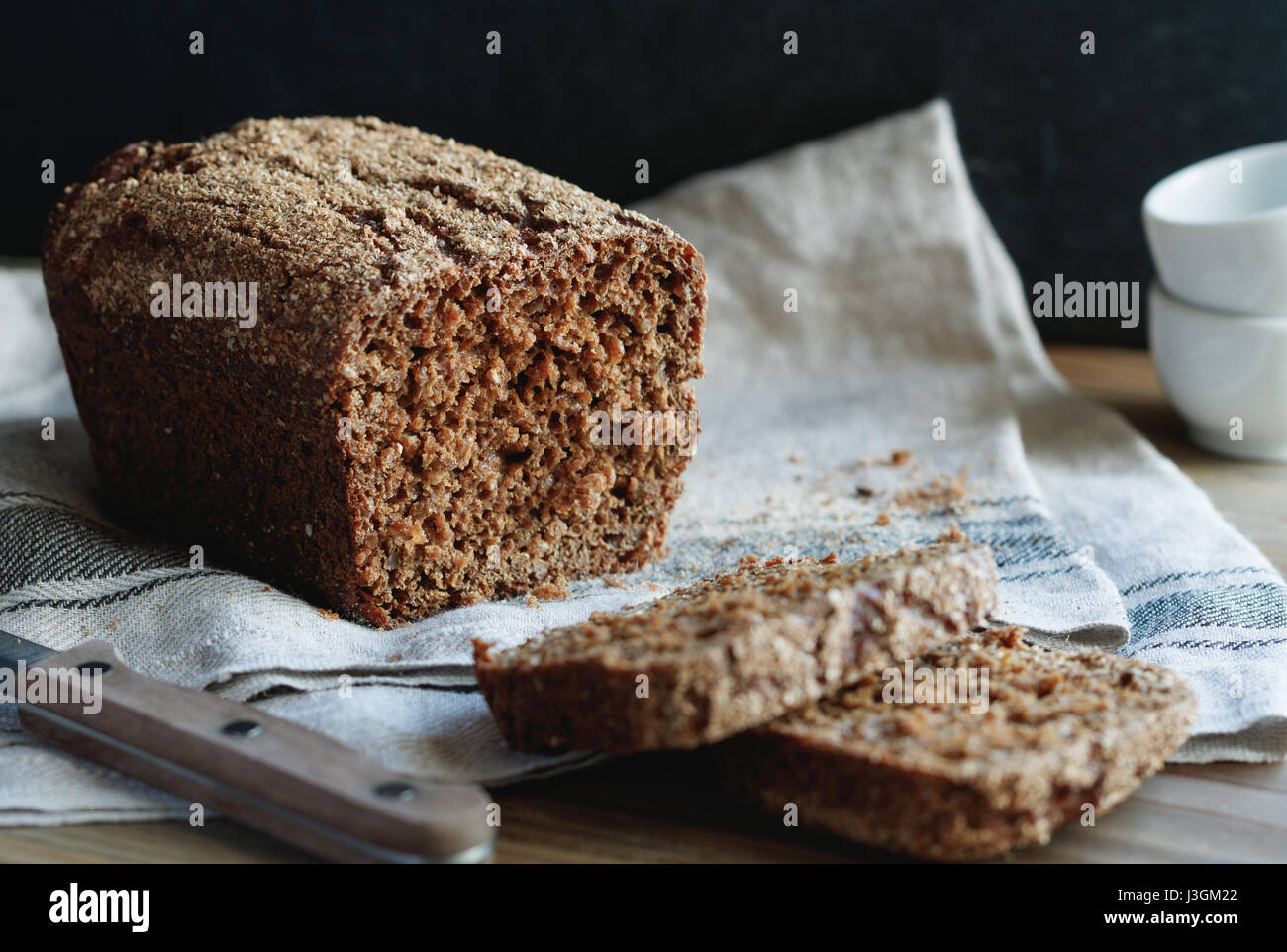 Close-up of loaf of grain rye bread on a wooden table. - Stock Image