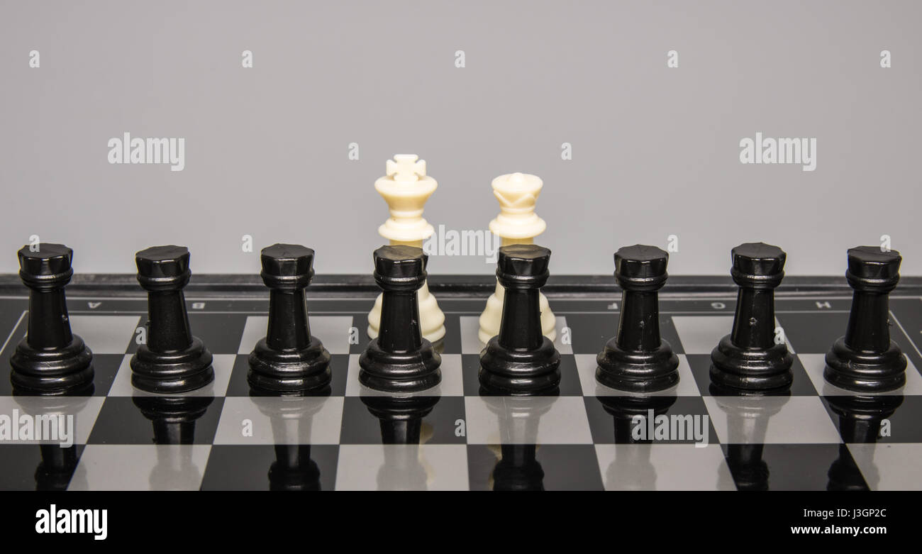 Concept - Eight black rooks are placed in front of a white queen  and king on a chess board - Stock Image