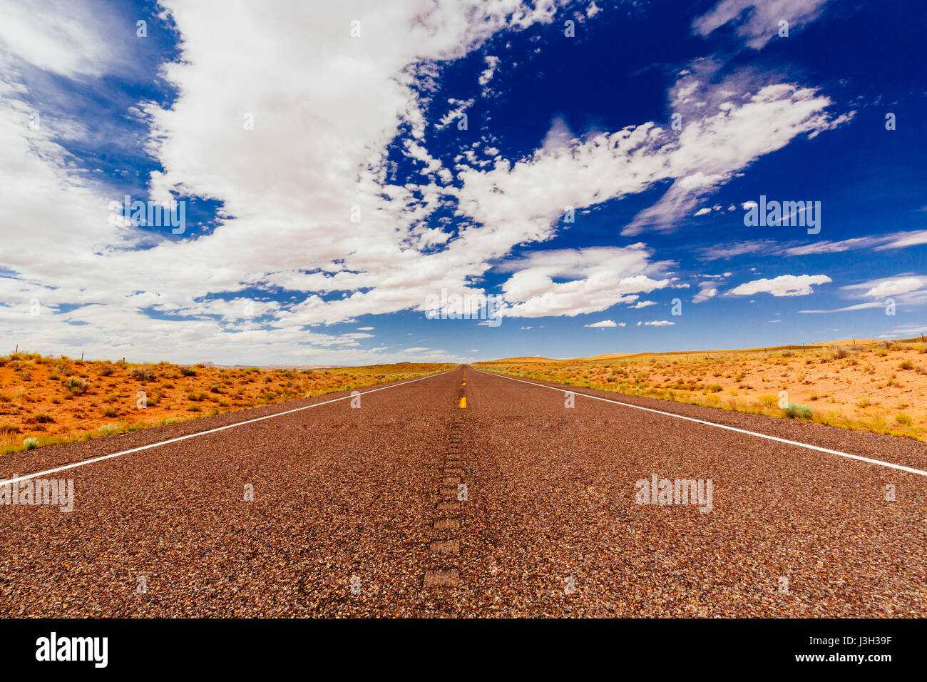 The road goes the distance. Perfectly smooth highway across the endless desert in Emery County, Utah, USA. - Stock Image