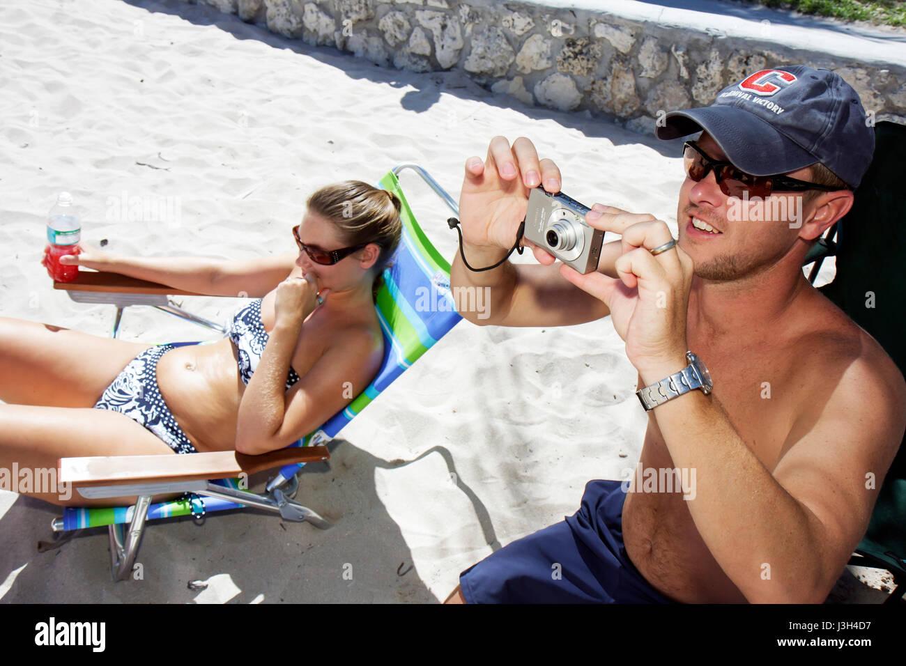 Miami Beach Florida Lummus Park man woman couple sunbather relax beach digital camera - Stock Image