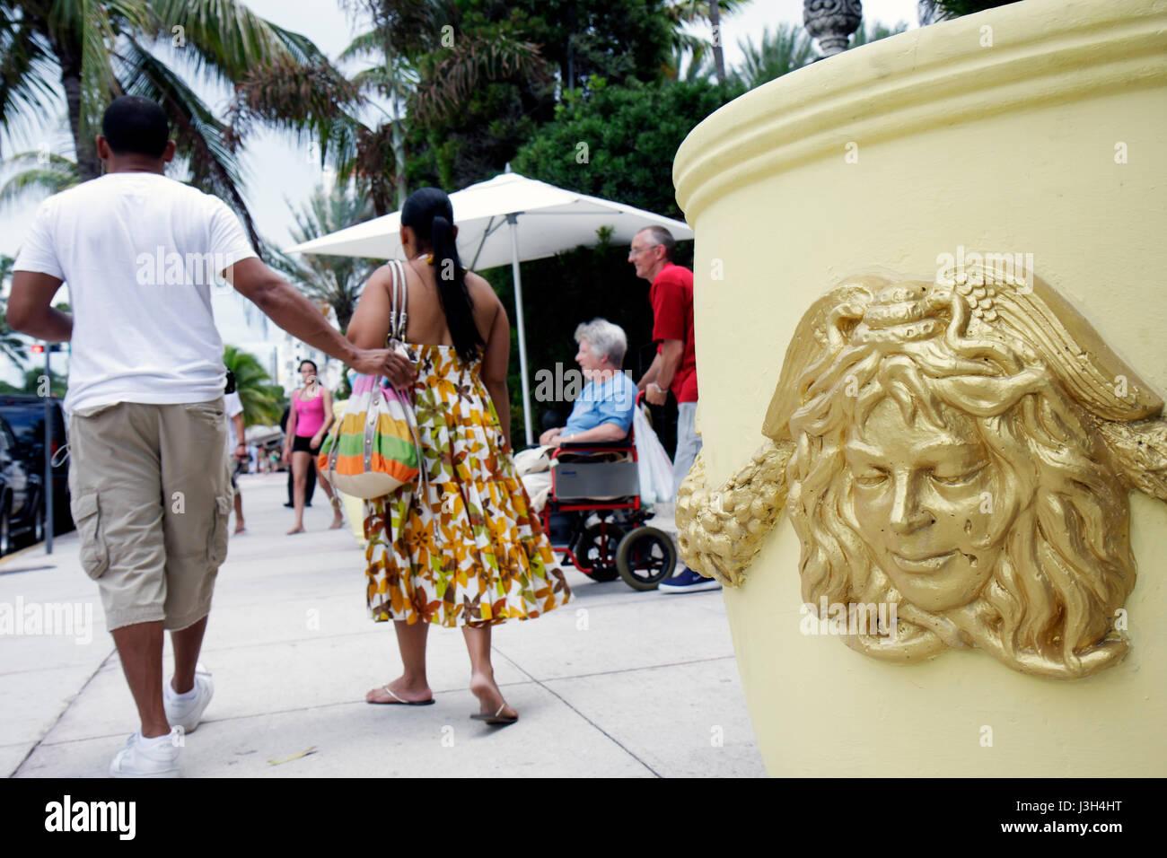 Miami Beach Florida Ocean Drive Casa Casuarina entrance Hispanic man woman couple ornamental planter sidewalk walking - Stock Image