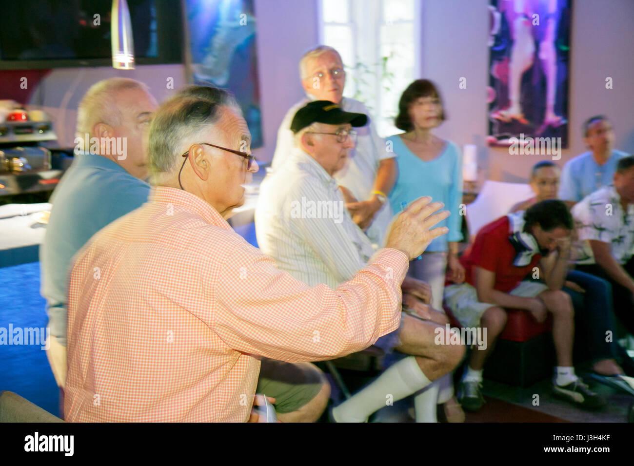 Miami Beach Florida Ocean Drive The Wave Hotel man men woman senior community meeting discussion speaks gestures - Stock Image