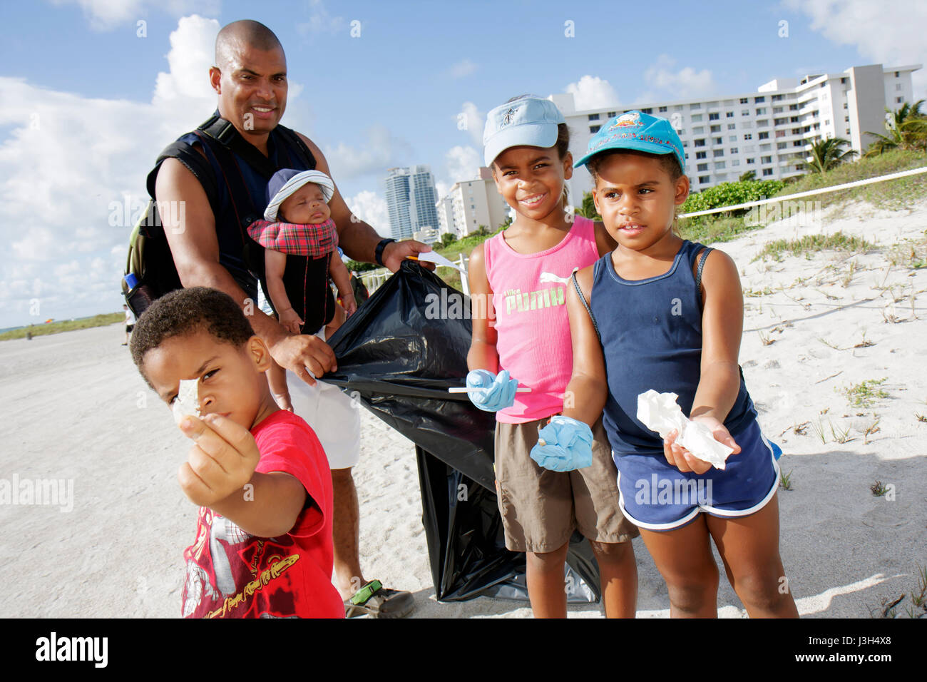 Miami Beach Florida International Coastal Cleanup volunteers Black man baby girls boy family father children environment - Stock Image