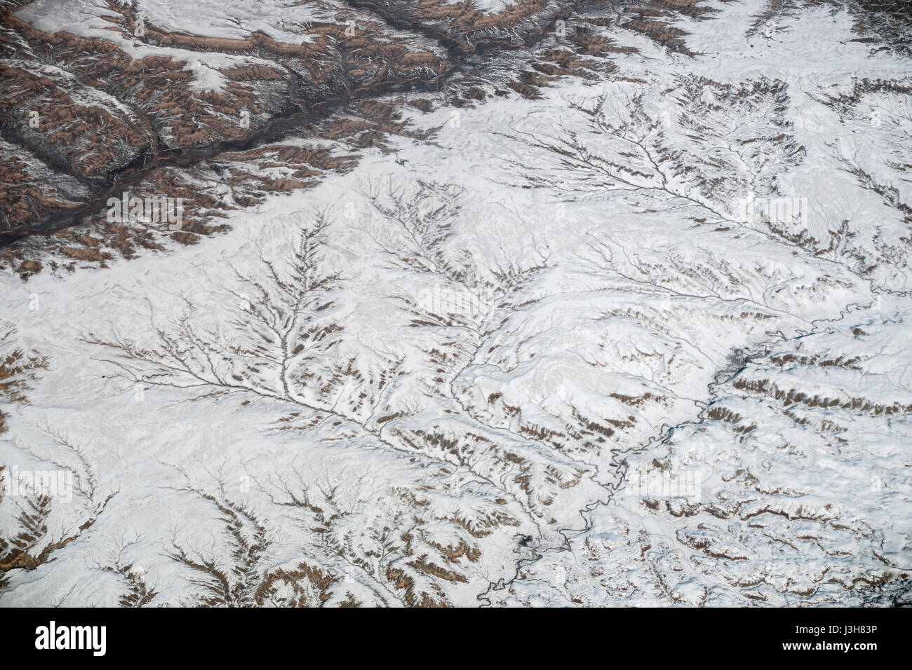 Aerial shot out of a plane flying above the USA, somewhere above the Rocky Mountains on a flight from Jackson Hole - Stock Image
