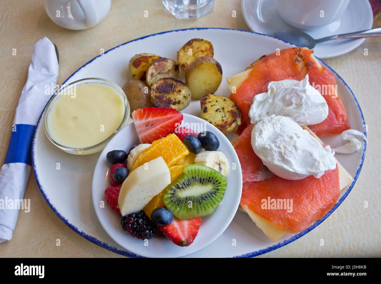 Delicious smoked salmon eggs benedict with fruit and potatoes.  Breakfast at Angelina's restaurant in New Westminster, - Stock Image