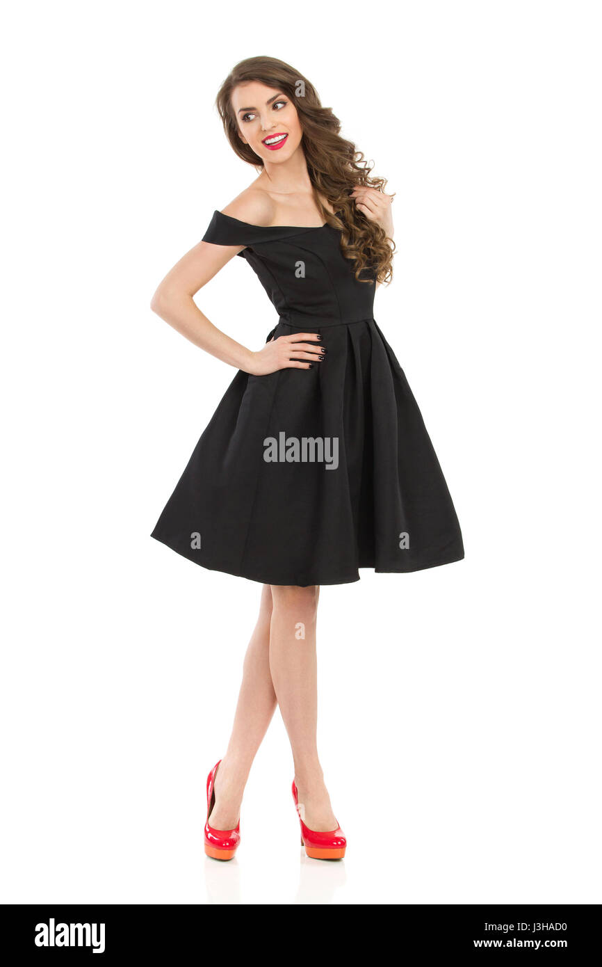 Beautiful young woman in elegant black cocktail dress and red high heels is holding hand on hip, looking away and - Stock Image