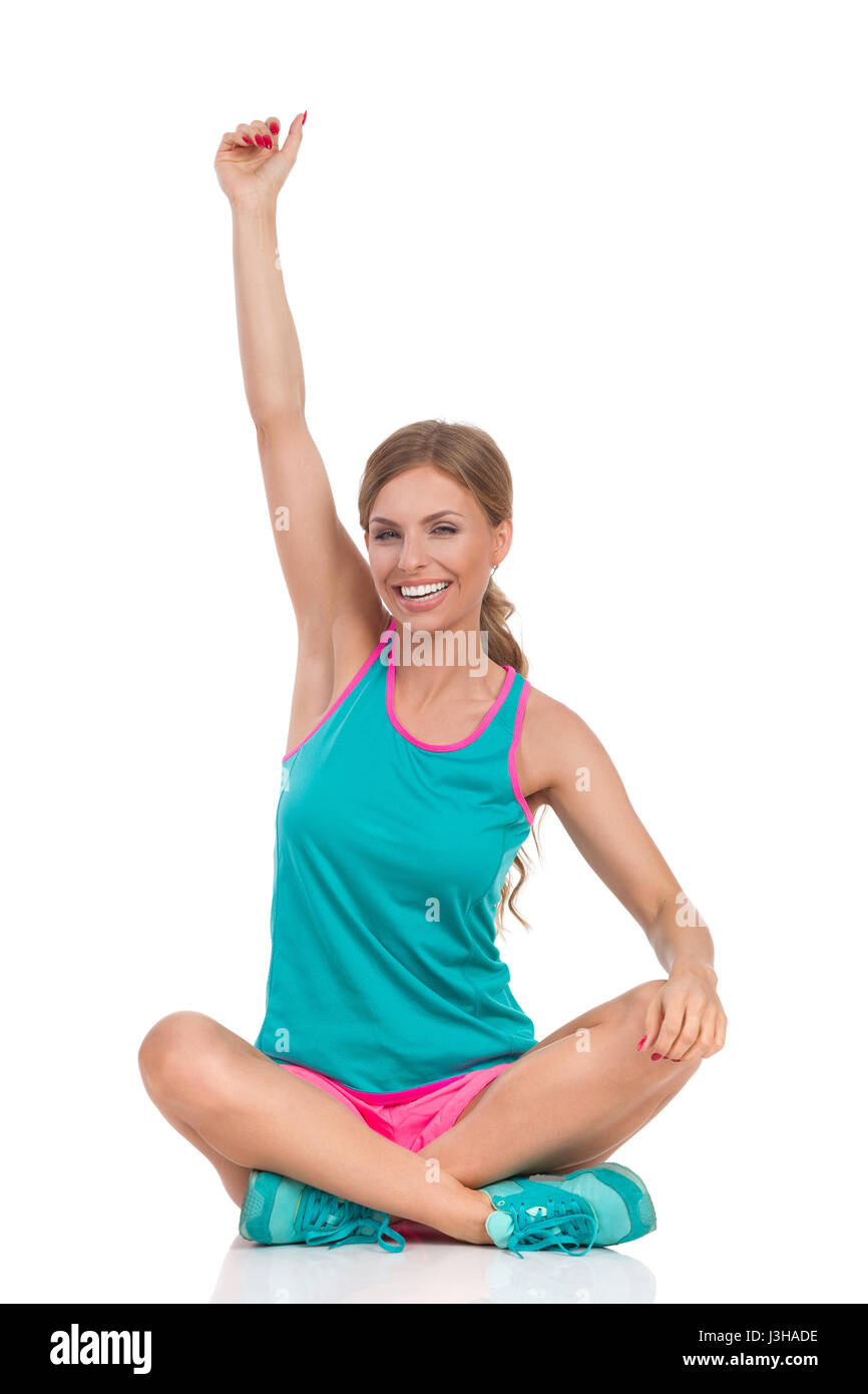 Beautiful young woman in vibrant sports clothes sitting on floor with legs crossed, smiling and rising arm. Full - Stock Image