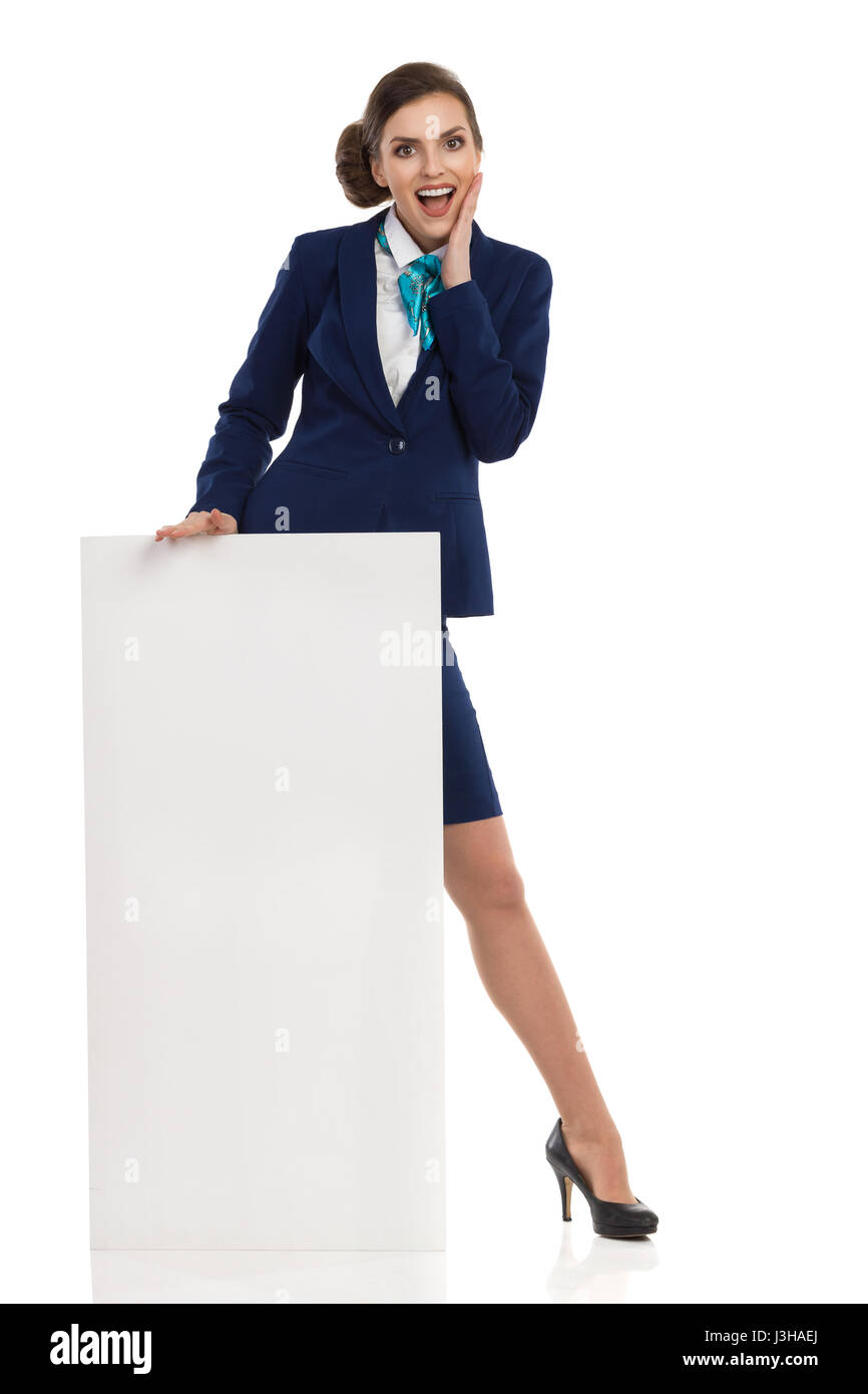 Young woman in blue formalwear and high heels, standing behind blank placard, holding hand on chin and shouting. - Stock Image