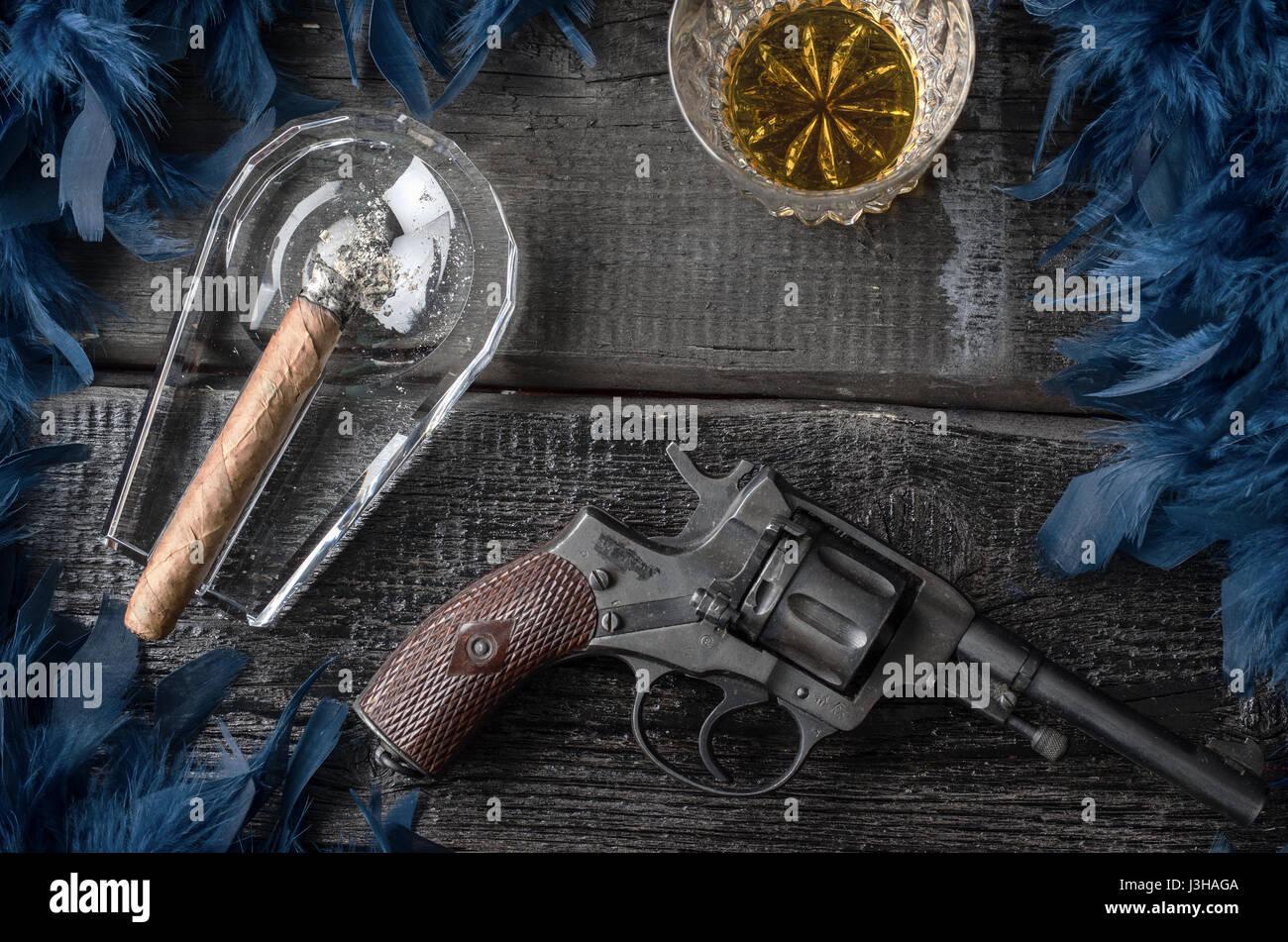 Thompson gun, revolver, cigar on ashtray, whiskey glass and blue feather boa - Stock Image