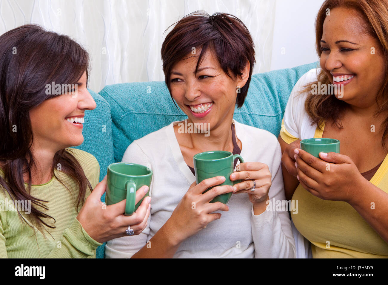 Diverse group of women talking and laughing. - Stock Image