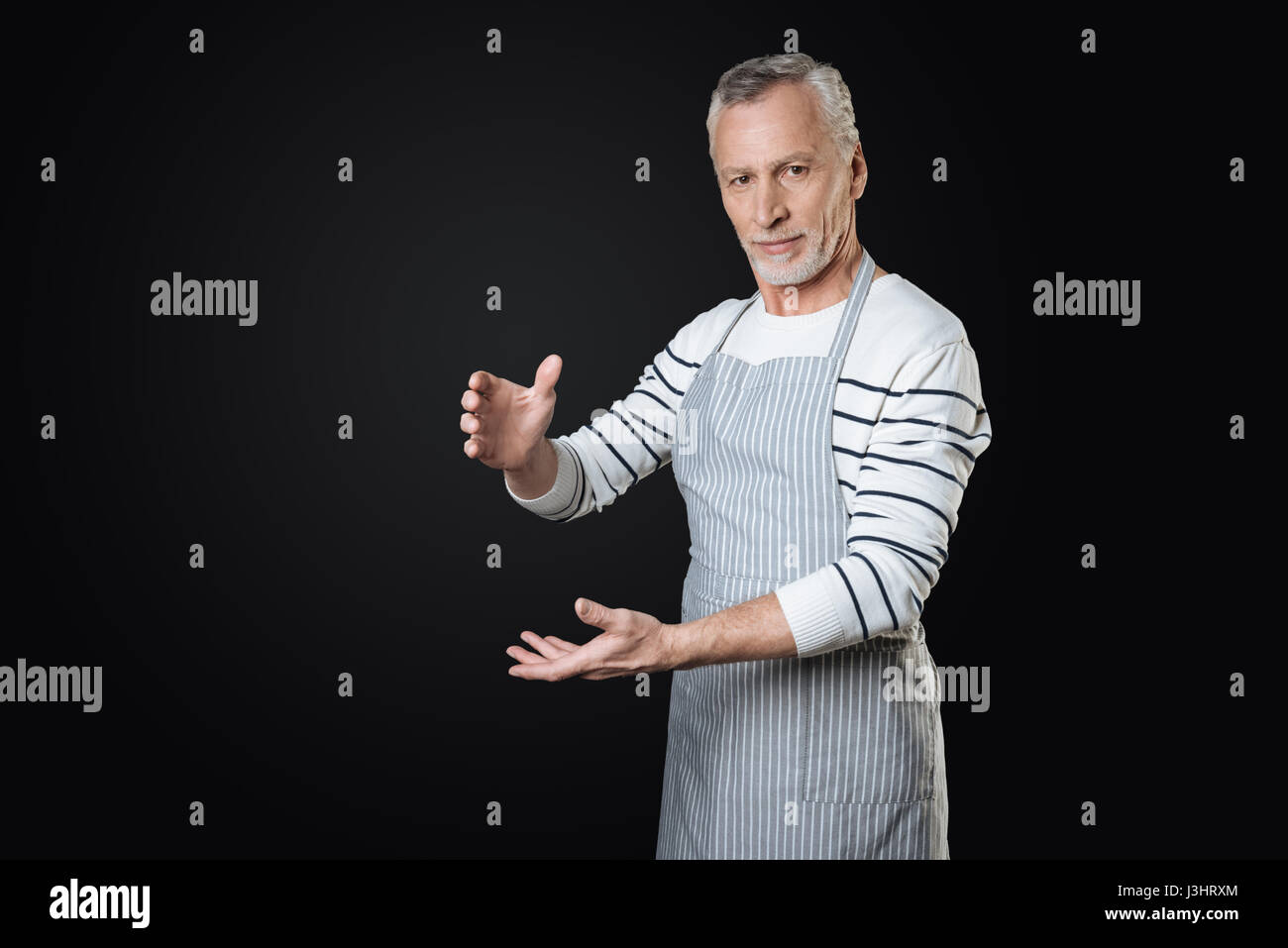 I have it. Delighted bearded gray-haired man wearing striped apron looking straight at camera standing over black Stock Photo