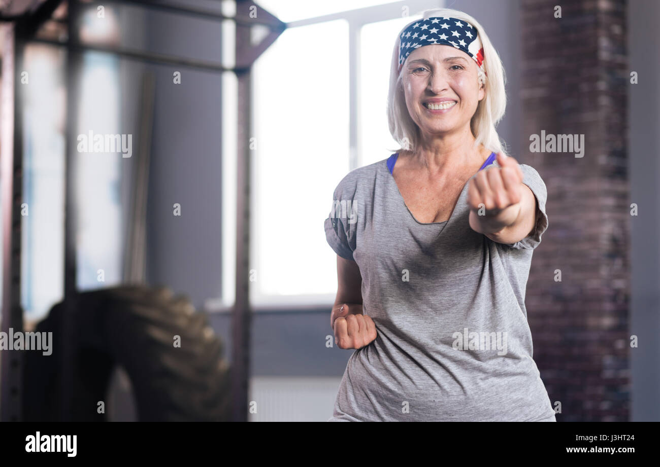 Self defence classes. Happy active senior woman clenching her fists and smiling while practicing fighting - Stock Image
