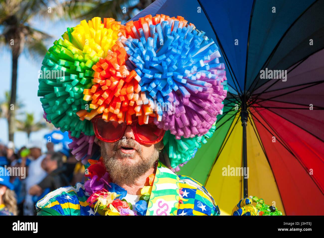 RIO DE JANEIRO - FEBRUARY 11, 2017: Brazilian man in flamboyant rainbow wig with matching umbrella celebrates carnival - Stock Image