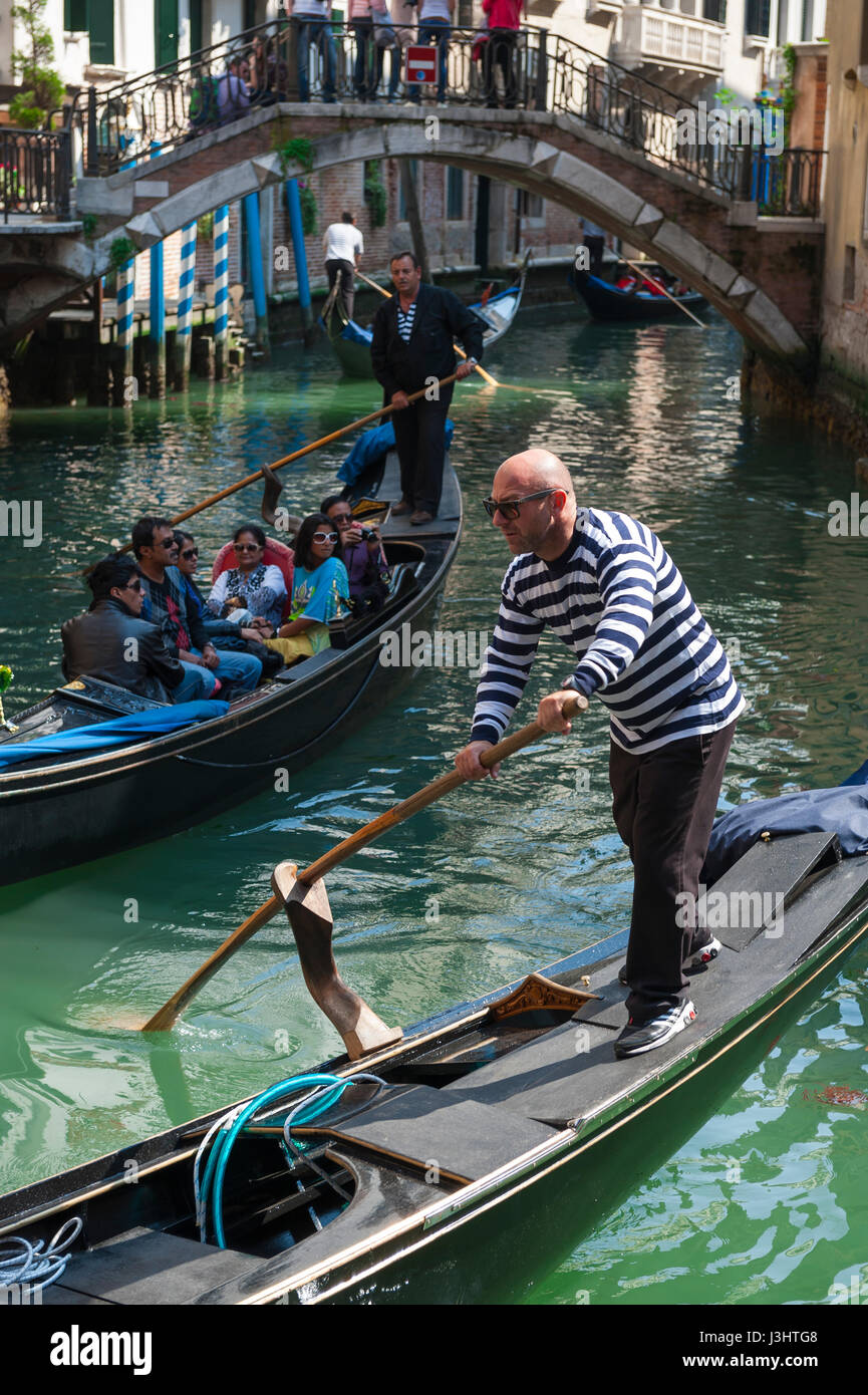 VENICE, ITALY - CIRCA APRIL 2013: Venetian gondolier punts his gondola along the green waters of a canal. - Stock Image