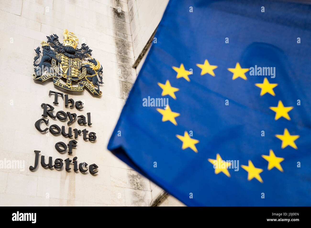 EU European Union flag flying in bright sun in front of the Royal Courts of Justice public building in London, United - Stock Image