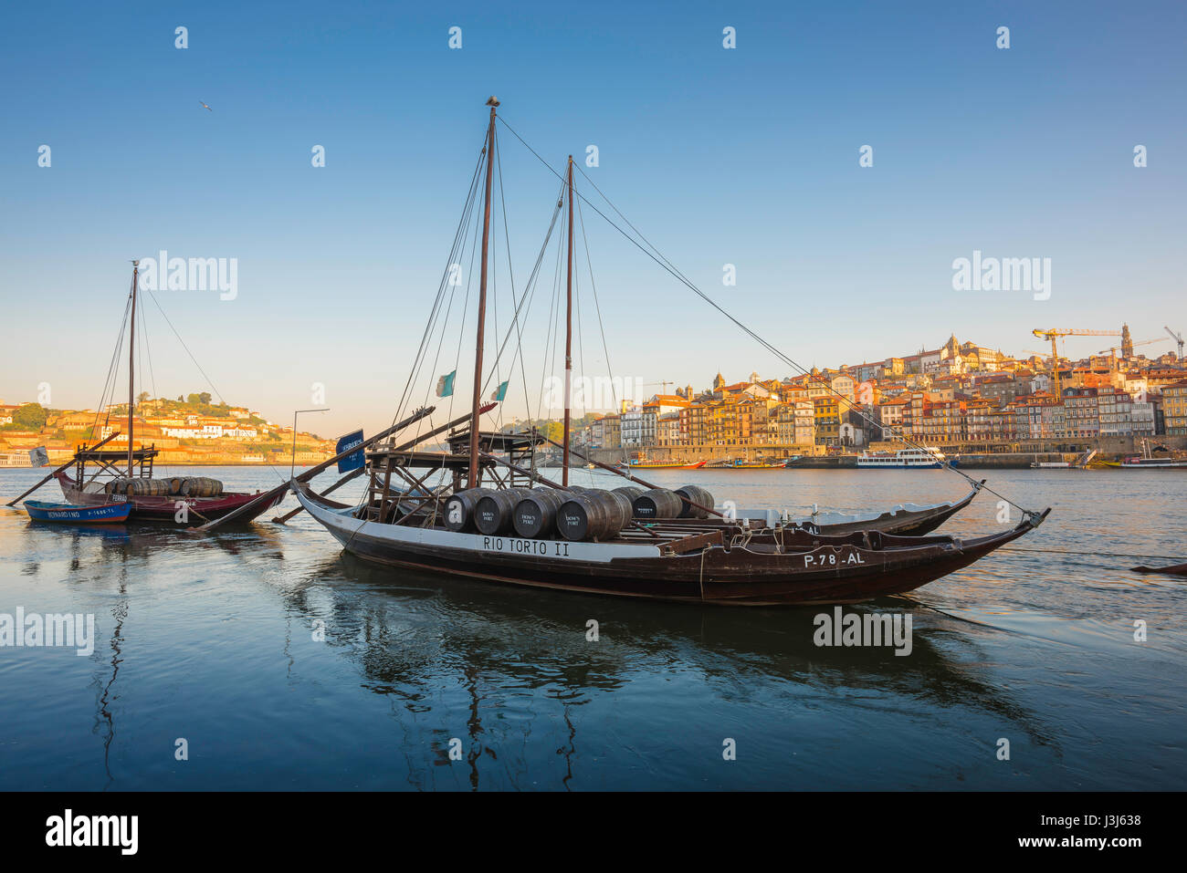 Porto Douro river, traditional rabelo boats on the Douro River with the skyline of Porto at sunrise in the background, Stock Photo