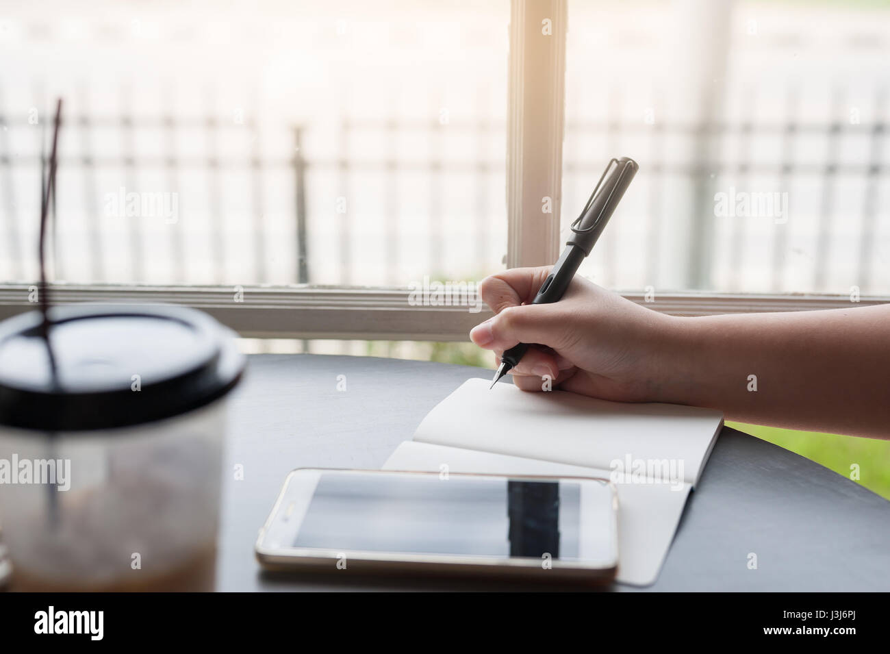Woman hand holding pen while writing on small notebook with smartphone on table beside window. Freelance journalist - Stock Image