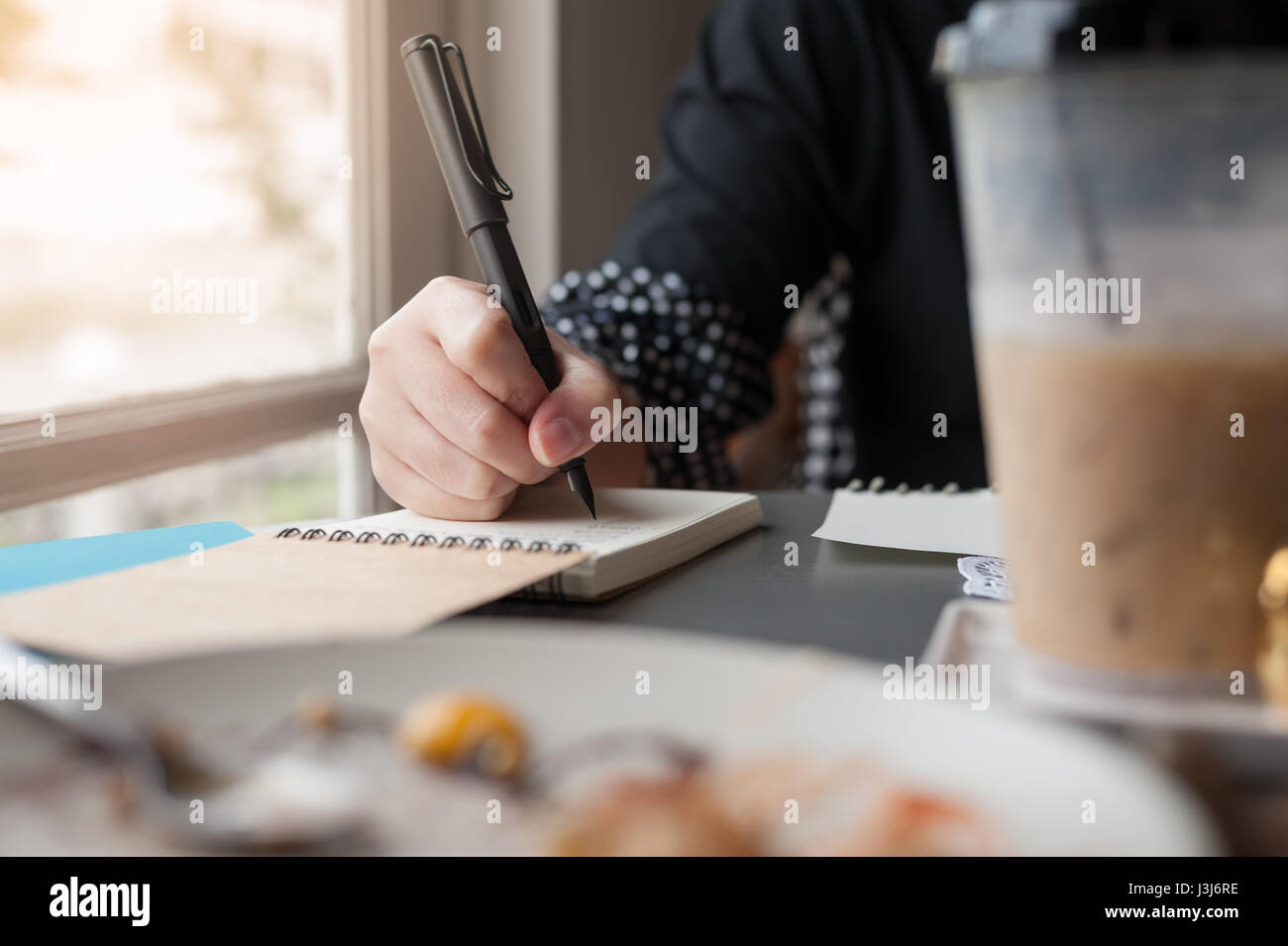 Woman hand holding pen while writing on small notebook beside window. Freelance journalist working at home concept. - Stock Image