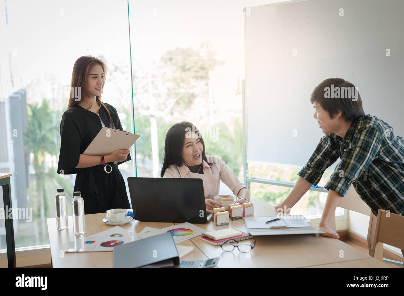 Asian businesspeople discussing and brainstorm with young freelance man in meeting room. Business company co-operate - Stock Image