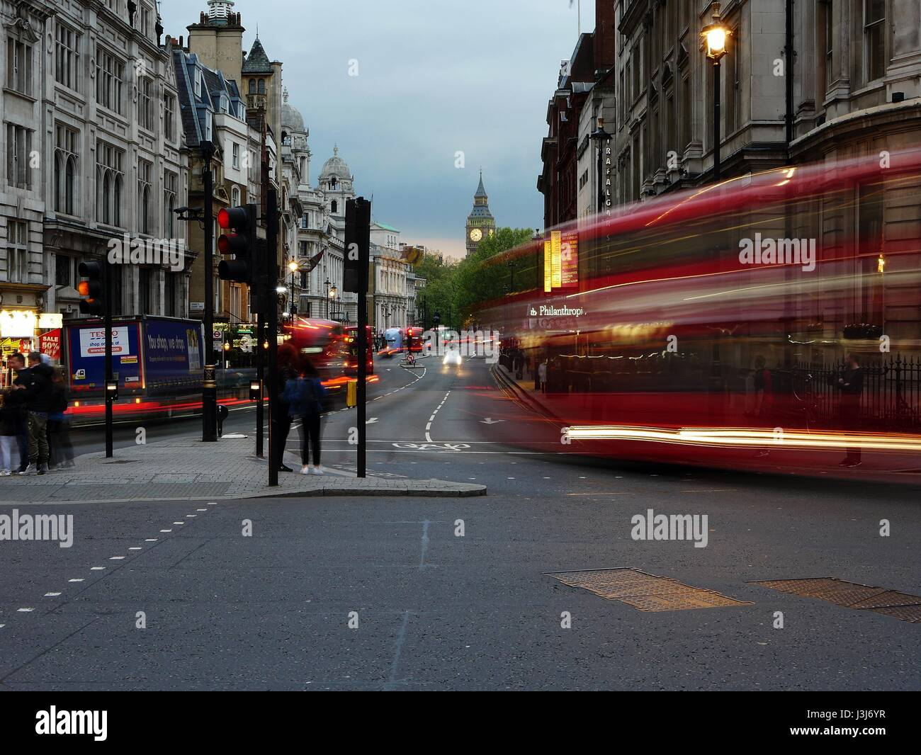 Light trails from cars and buses at Trafalgar Square, London, UK. Night time - Big Ben in background Stock Photo