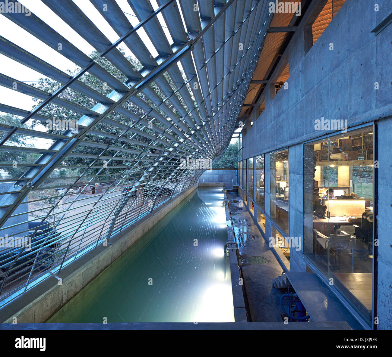 Entrance area under steel canopy with pool towards dusk. The Pool Studio of Matharoo Associates, Ahmedabad, India. - Stock Image