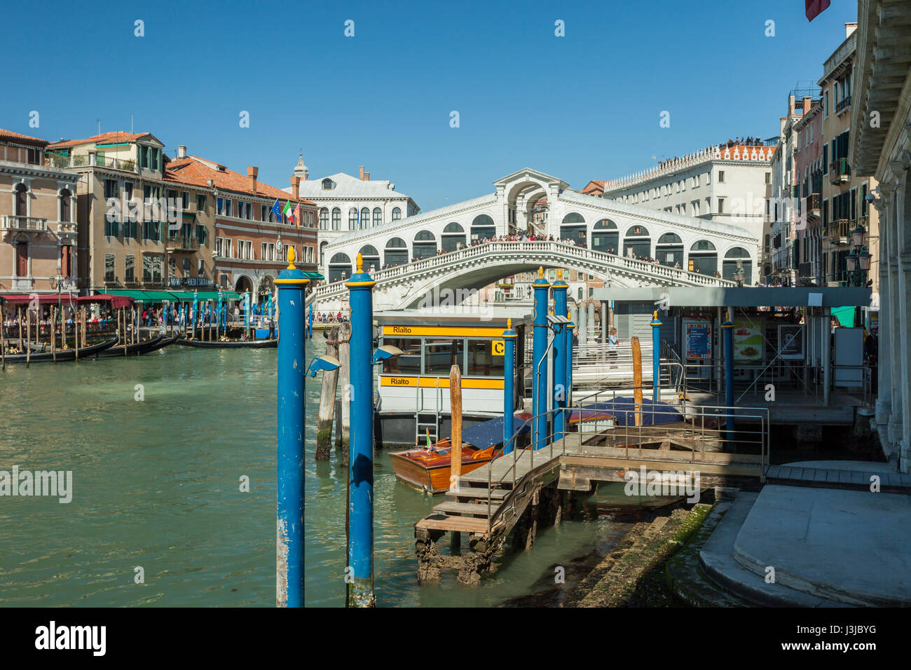 Spring afternoon on Grand Canal in Venice. Rialto Bridge in the distance. - Stock Image