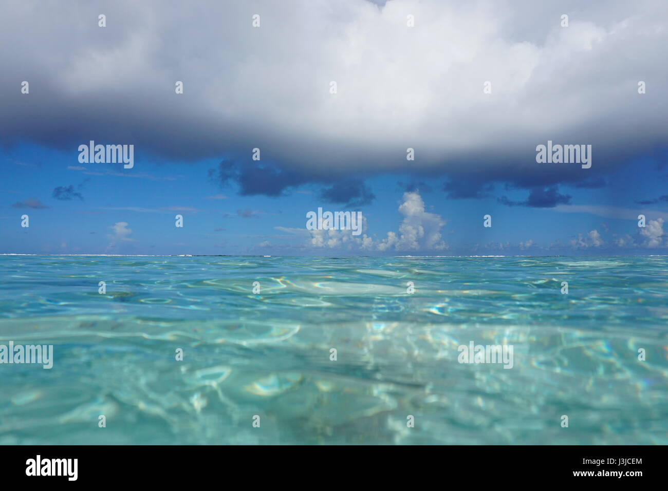Seascape cloudy blue sky with turquoise water of the lagoon of Bora Bora, seen from sea surface, French Polynesia, - Stock Image