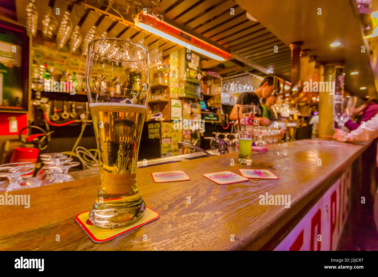 BRUSSELS, BELGIUM - 11 AUGUST, 2015: Glass of beer sitting on bar counter inside Delirium Bar, selection of other Stock Photo