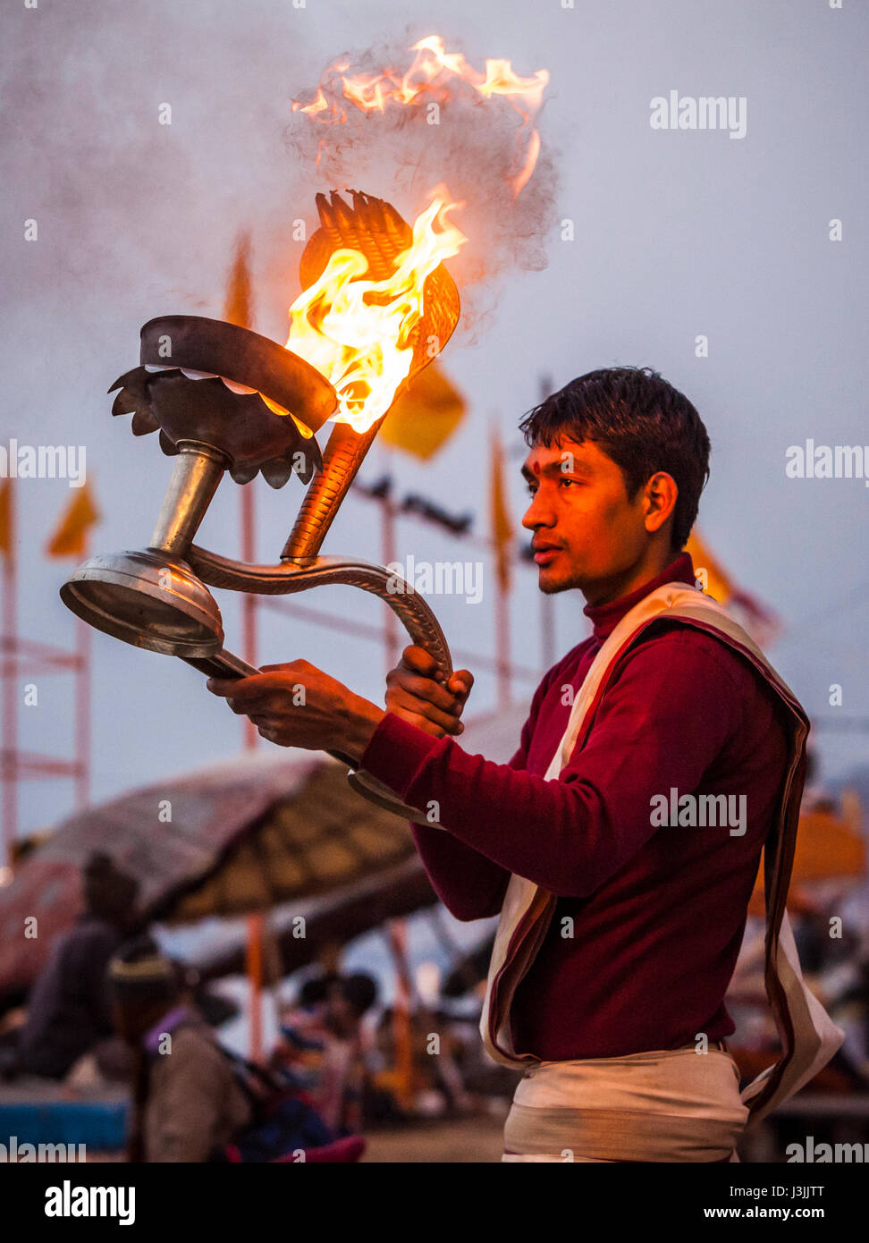 A Hindu priest on the shores of the Ganges / Ganga river in Varanasi, India performs a ceremony (puja) with an oil - Stock Image