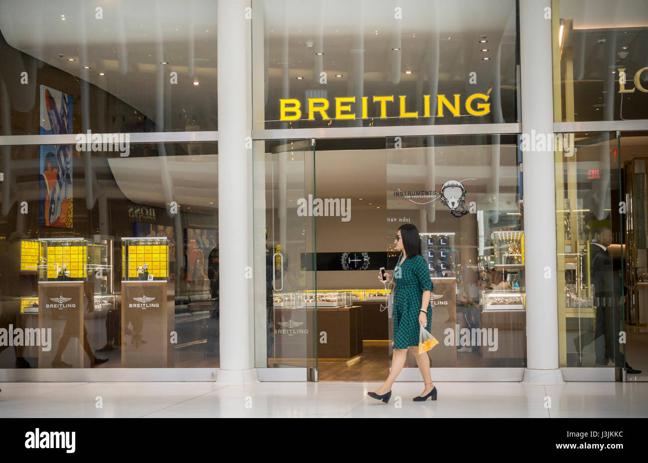 People walk past a Breitling retail store in New York on Saturday, April 29, 2017. CVC Capital Partners, a private - Stock Image