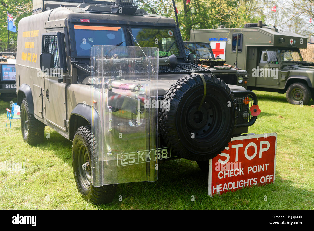 Army Landrover painted green, with a riot shield and 'STOP. Check point. Headlights off' sign, commonly - Stock Image