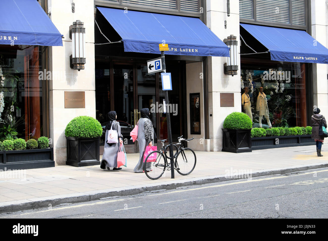 Muslim women shoppers in hijabs with shopping bags walking past American Ralph Lauren store in New Bond Street, - Stock Image