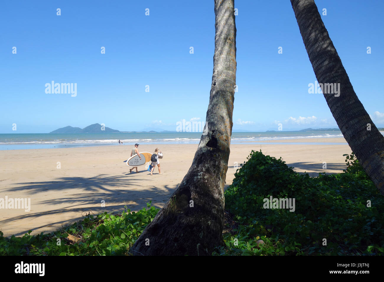 People walking along Mission Beach with Dunk Island in background, Queensland, Australia. no MR - Stock Image