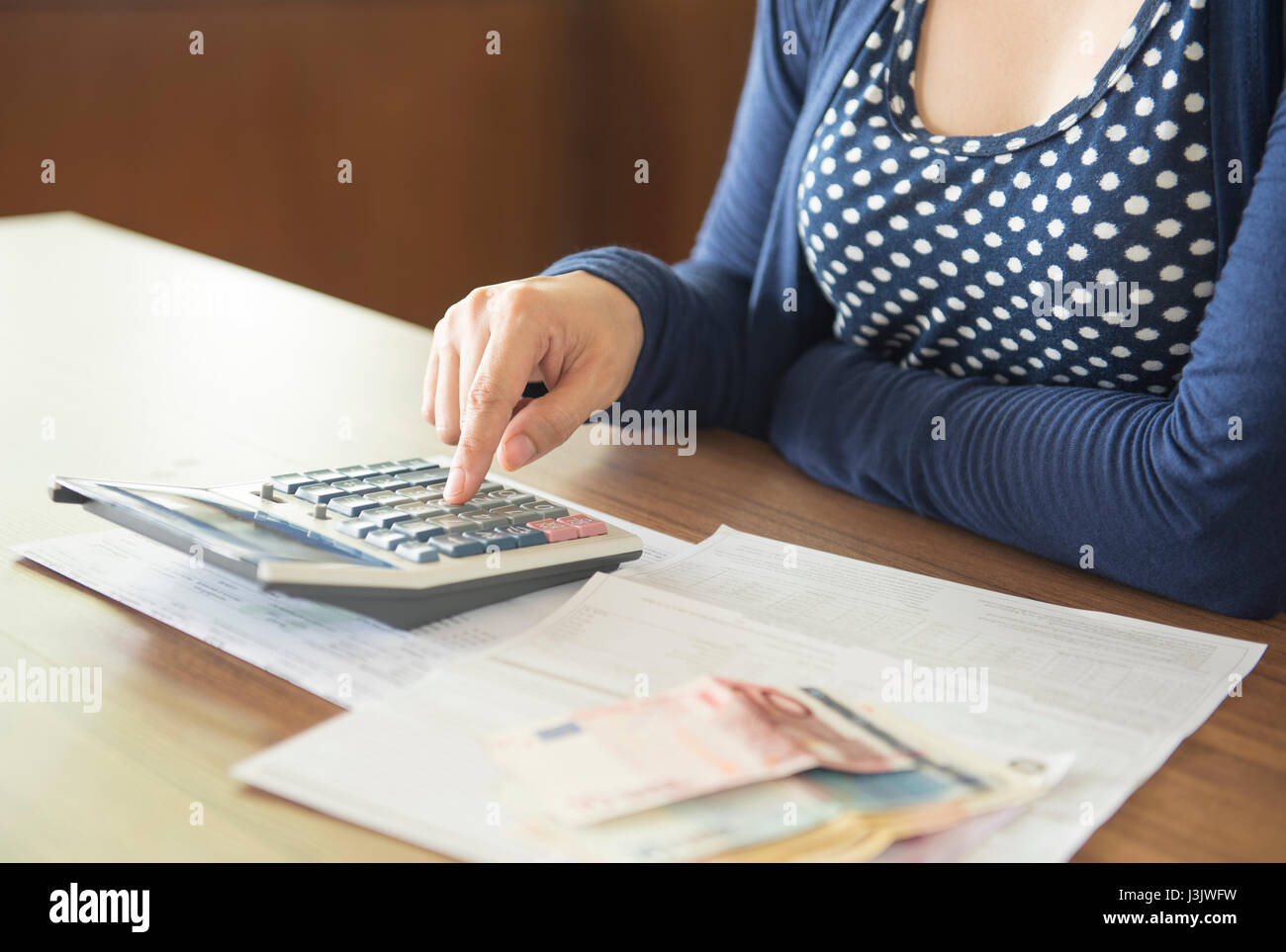 Women are calculating calculator to determine the cost to the invoice. - Stock Image