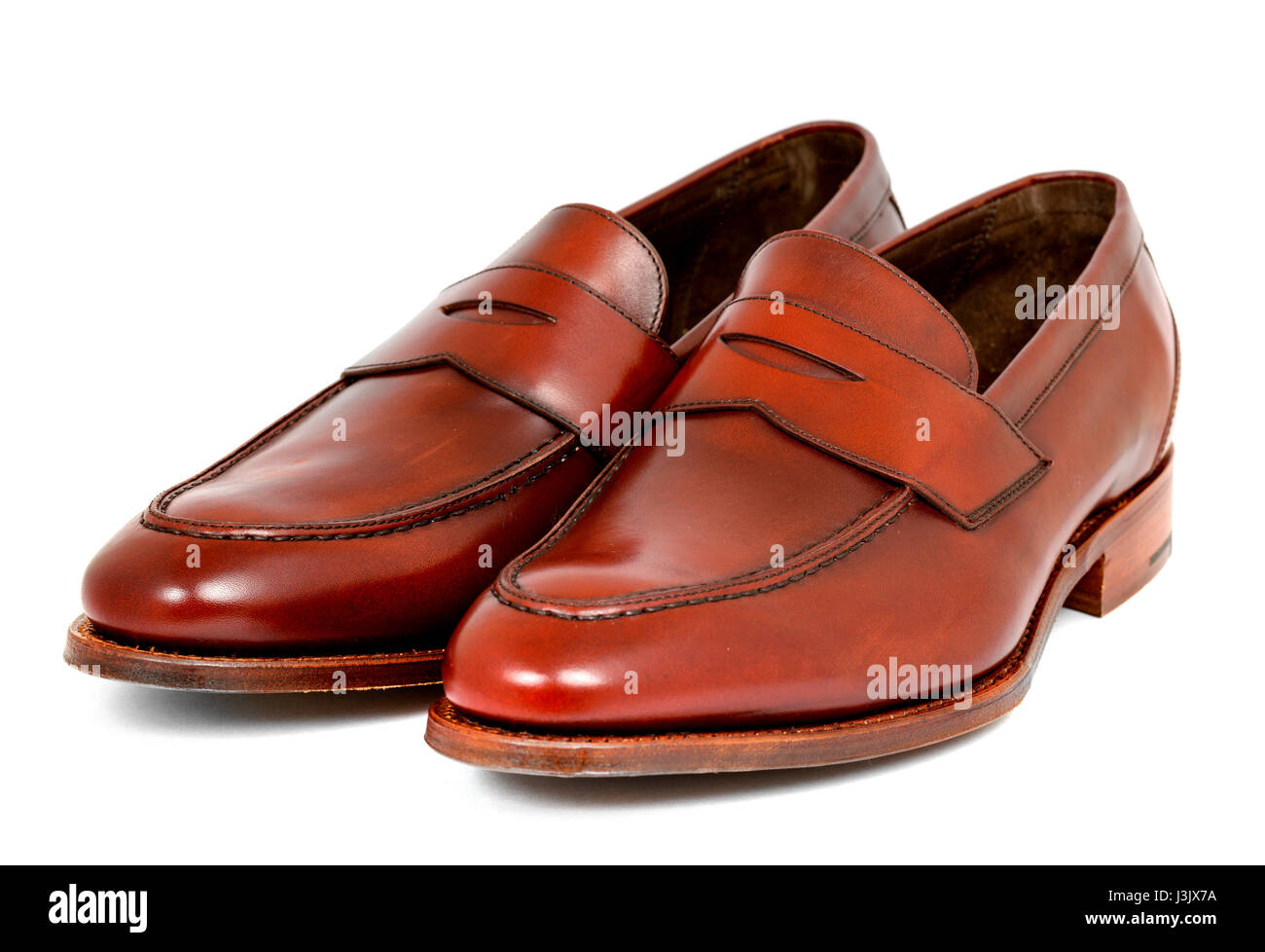 Pair of leather burgundy penny loafer shoes together on white background. Horizontal image diagonal left - Stock Image