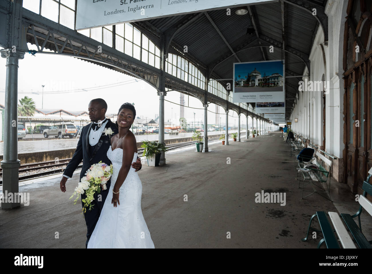 A newly wed couple take shelter from the rain at the historic Caminho de Ferro de Mocambique Maputo railway station - Stock Image