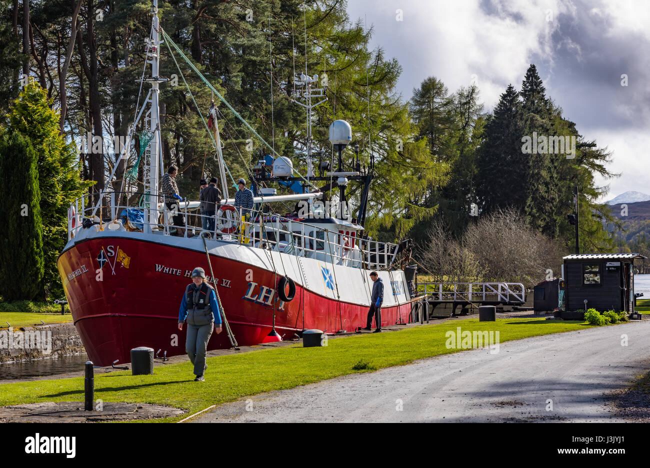Kytra lock with motor vessel & lock keeper, Caledonian Canal, Highlands, Scotland, UK. Stock Photo