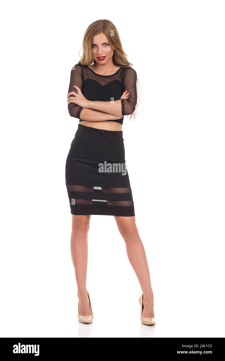 Beautiful blond young woman in black dress posing with arms crossed and looking at camera. Full length studio shot - Stock Image