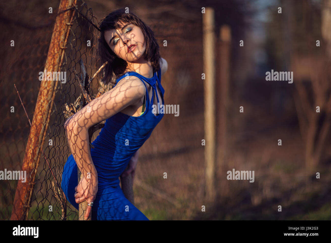 Beautiful girl in evening dress blue backs pressed against the fence. - Stock Image