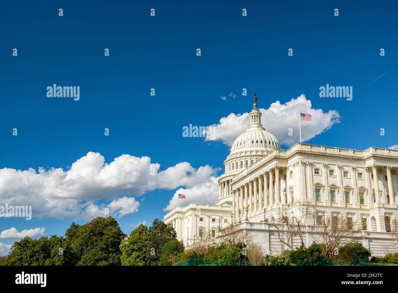U.S. Capitol with flags, blue sky and clouds - Stock Image