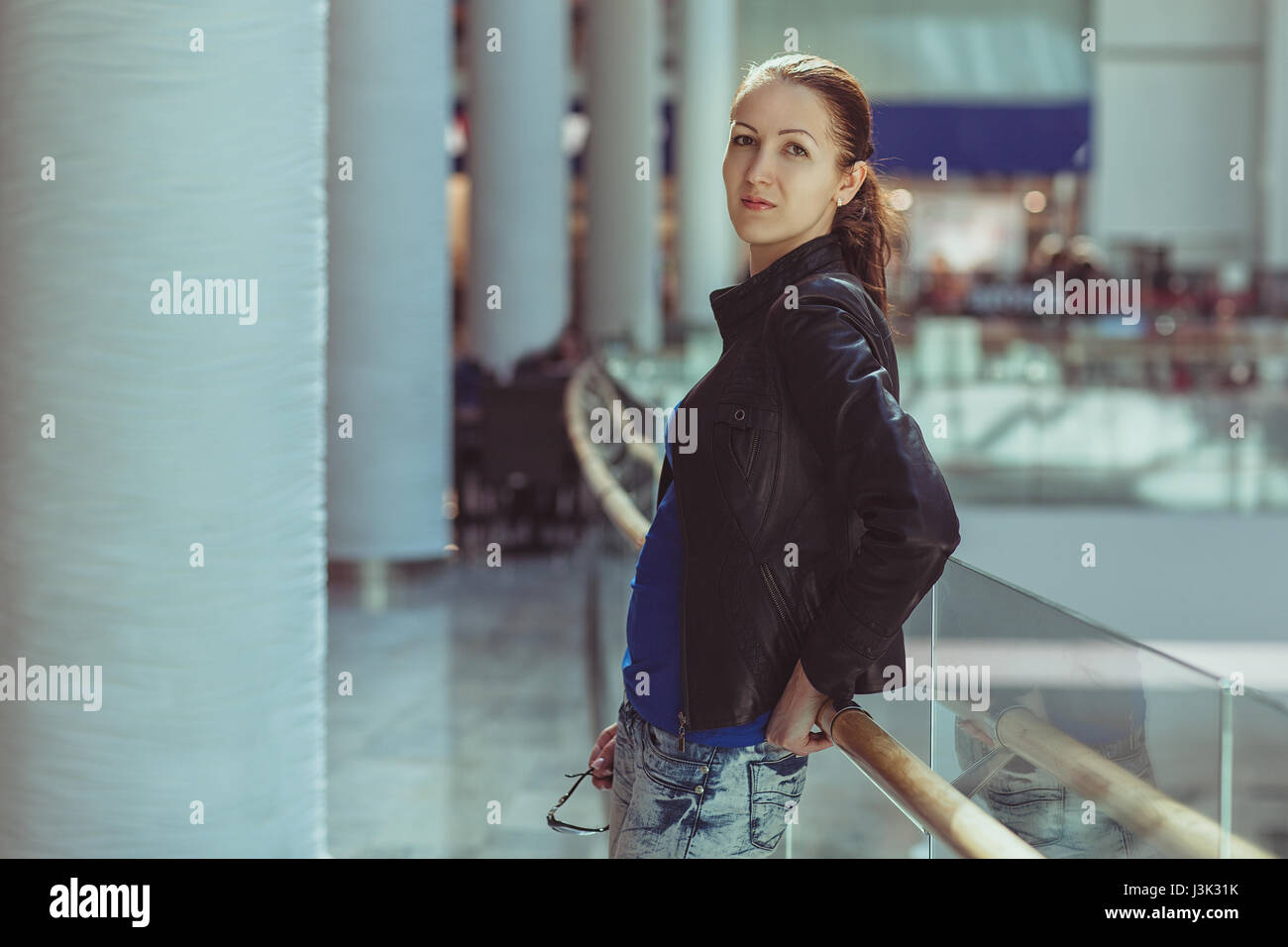 Beautiful girl with glasses daydreaming in a large store. - Stock Image