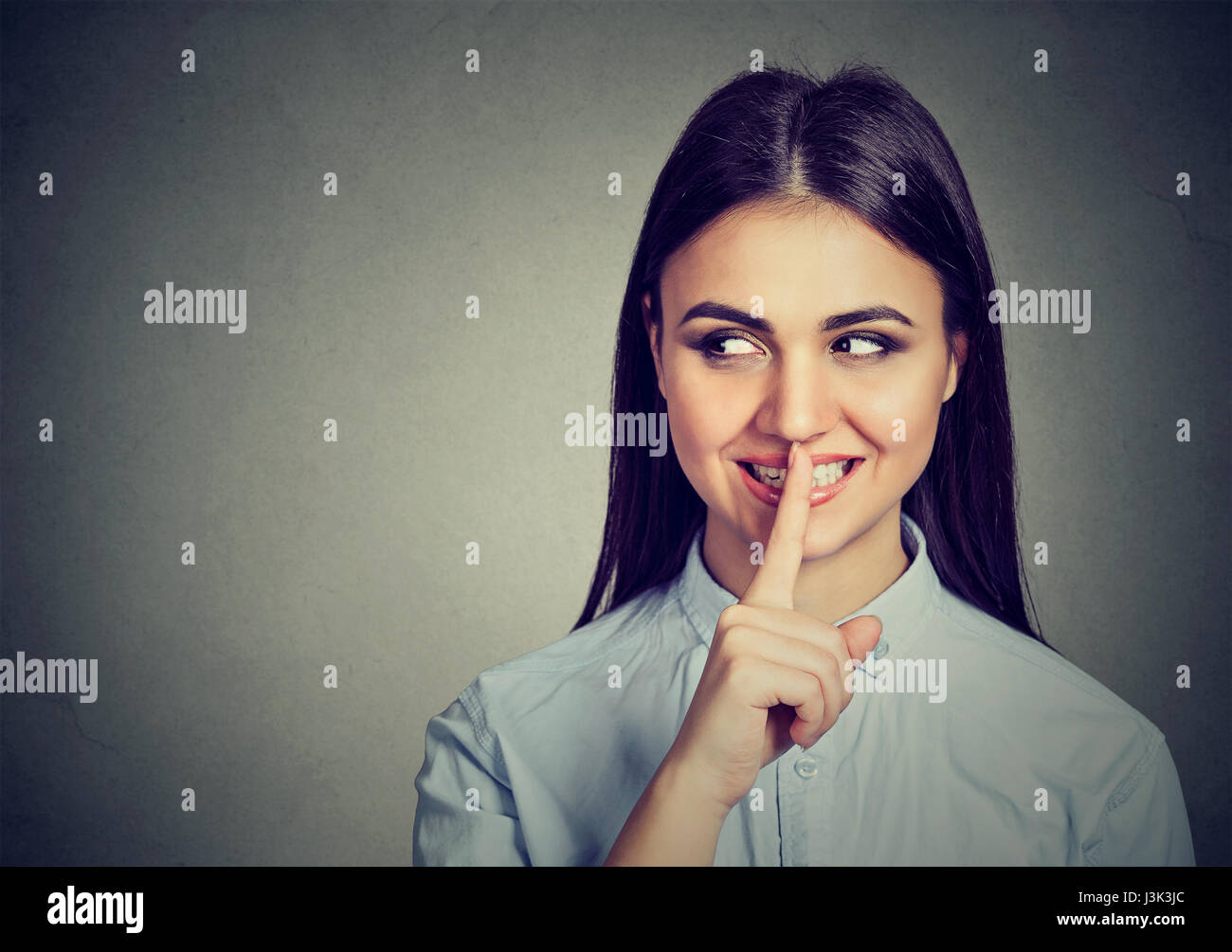 Happy secret girl. Woman saying hush be quiet with finger on lips gesture isolated on gray wall background. - Stock Image