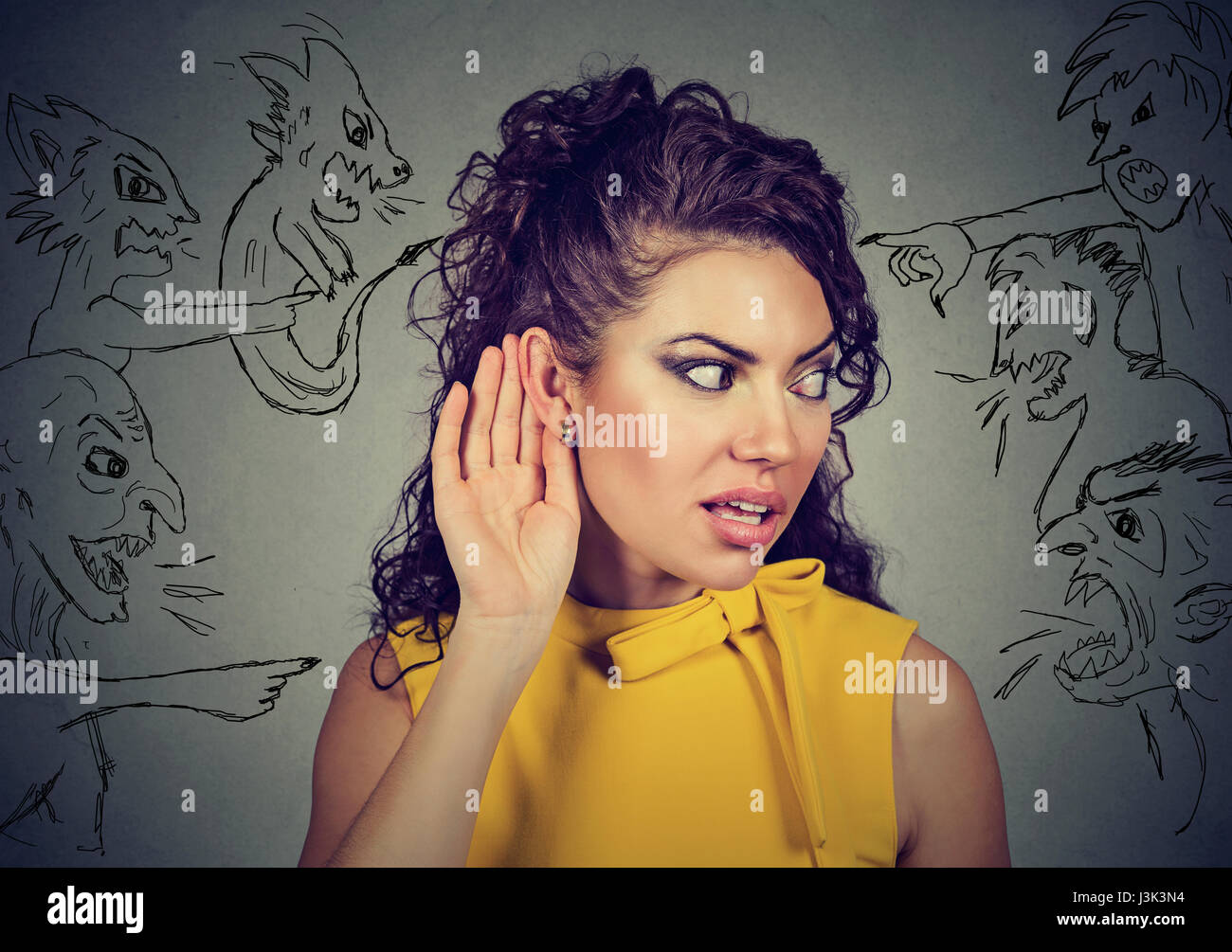 Closeup young woman holds her hand near ear and listens carefully to evil voices isolated on gray wall background. - Stock Image